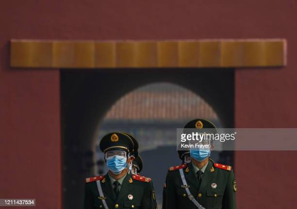 Chinese paramilitary police wear protective masks as they guard the entrance to the Forbidden City as it re-opened to limited visitors for the May...