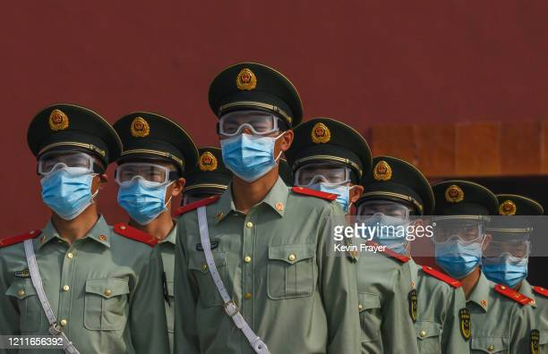 Chinese paramilitary police wear protective masks as they guard the entrance to the Forbidden City as it reopened to limited visitors for the May...