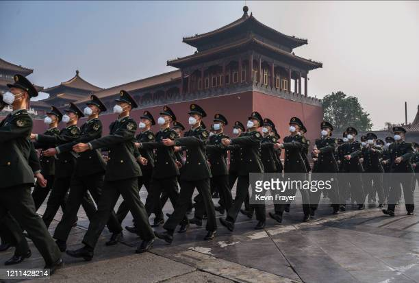 Chinese paramilitary police wear protective masks as they march by the entrance to the Forbidden City as it re-opened to limited visitors for the May...