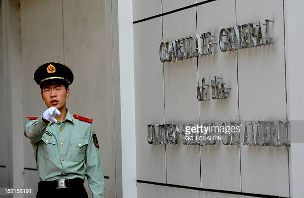 Chinese paramilitary policeman gestures to photographers at the entrance to the US consulate in Chengdu, southwest China's Sichuan province on...