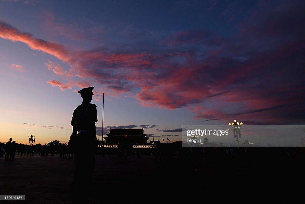 A Chinese paramilitary policeman guards at Tiananmen Square under crimson clouds at sunset after several days of heavy air pollution on July 4, 2013 in Beijing, China.