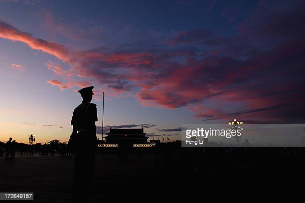 Chinese paramilitary policeman guards at Tiananmen Square under crimson clouds at sunset after several days of heavy air pollution on July 4 2013 in...