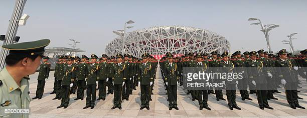 Chinese paramilitary policeman line up at a military parade rehearsal outside the Olympic Stadium known as the 'Bird's Nest' in Beijing on July 22...