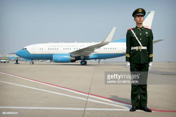 Chinese paramilitary policeman stands guard as a plane carrying US Secretary of State Rex Tillerson arrives at Beijing Capital International Airport...
