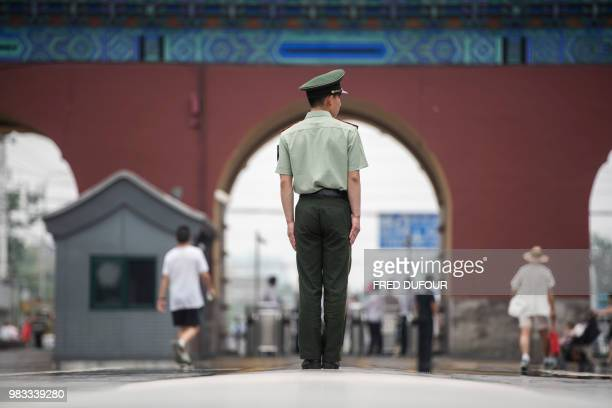 Chinese paramilitary policeman stands guard prior to the arrival of French Prime Minister Edouard Philippe for a private visit at the Temple of...