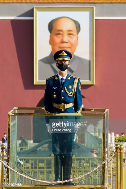 Chinese paramilitary policeman wears a protective mask stands in front of a portrait of late communist leader Mao Zedong reacts during a national...