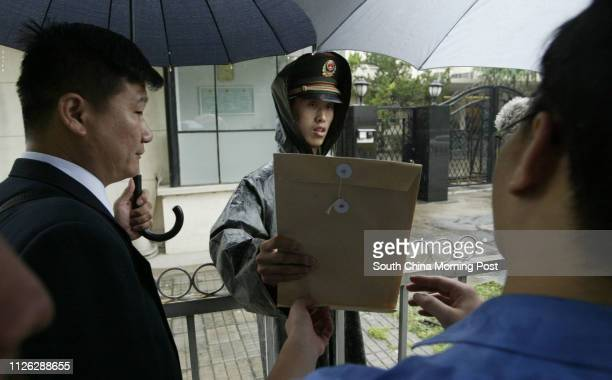 A Chinese Paramilitary Policeman who is guarding the Japanese Embassy in Beijing China takes a look at a petition containing over 300 000 signitures...