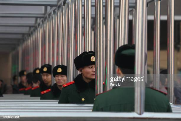 Chinese paramilitary policemen guard at the entrance of the check-in kiosks for real-name tickets at Beijing West Railway Station on January 8, 2012...