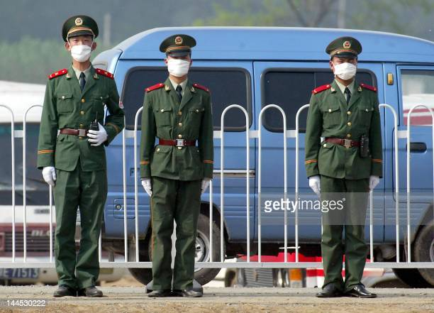 Chinese paramilitary policemen guard the perimeter of the hospital erected in barely a week to house a rapidly increasing number of Chinese patients...