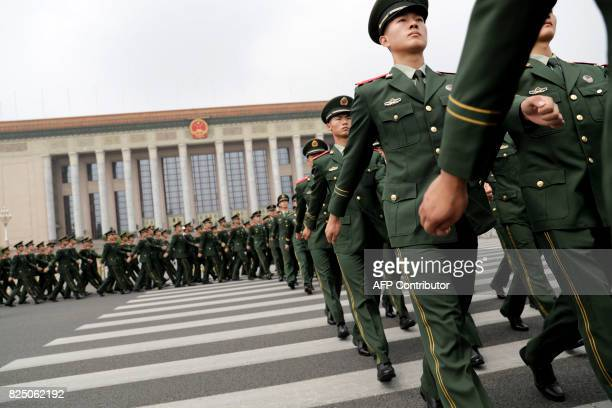 Chinese paramilitary policemen march outside the Great Hall of the People after attending a ceremony to commemorate the 90th anniversary of the...