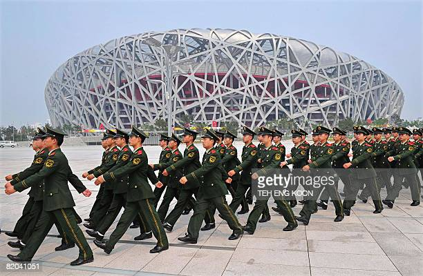 Chinese paramilitary policemen march past the Beijing Olympic Games security in front of the National Stadium better know as the 'Bird's Nest' in...