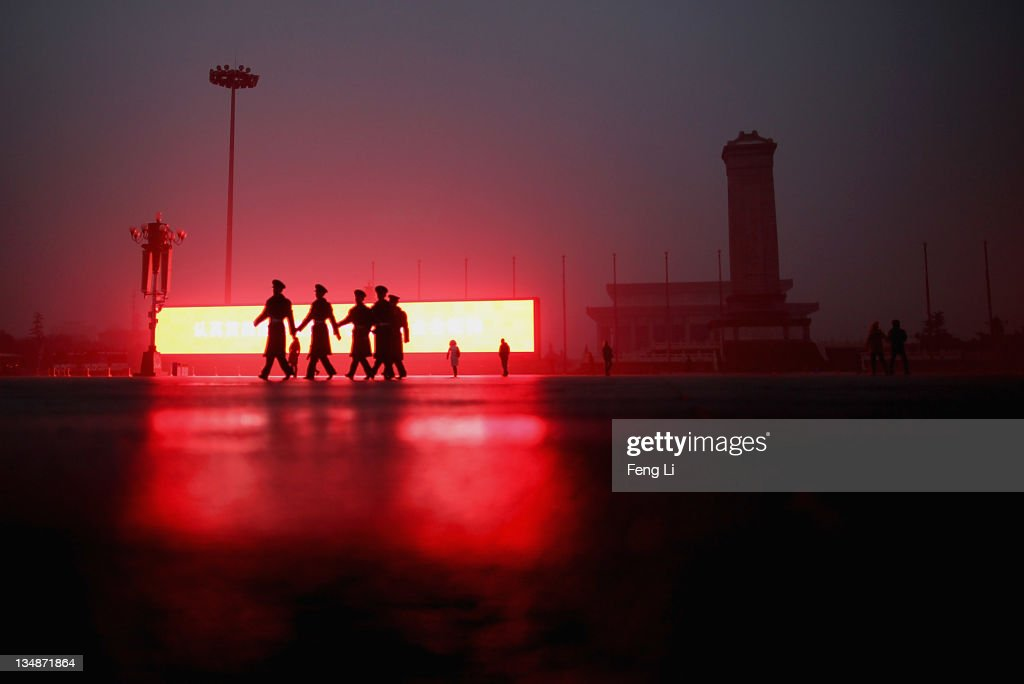 Chinese paramilitary policemen pass a LED screen on the Tiananmen Square in fog on December 5, 2011 in Beijing, China. Dense fog hit northern and eastern China on Sunday, causing major traffic jams and delayed flights.