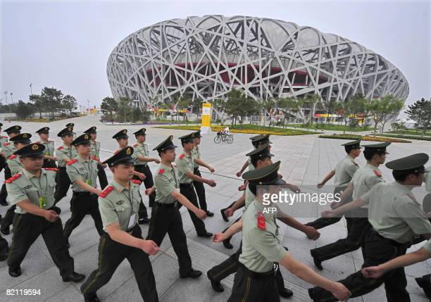 Chinese paramilitary policemen patrol in front of the National Stadium, better know as the Bird's Nest, on the Olympic Green in Beijing on July 30,...