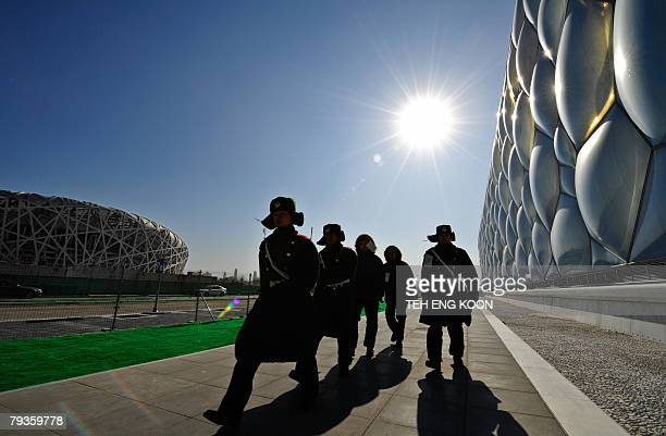 Chinese paramilitary policemen patrol past the blue bubble-wrapped structure of the National Aquatics Centre near the National Stadium in Beijing, 29...