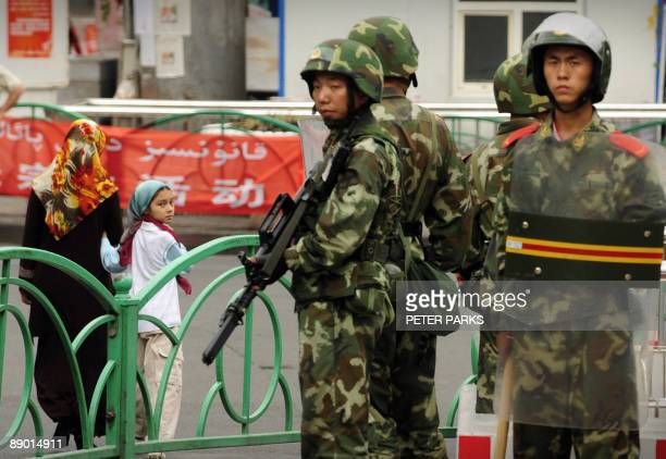 Chinese paramilitary policemen stand guard on a street in the Uighur district of Urumqi city in China's Xinjiang region on July 14 2009 A mosque was...