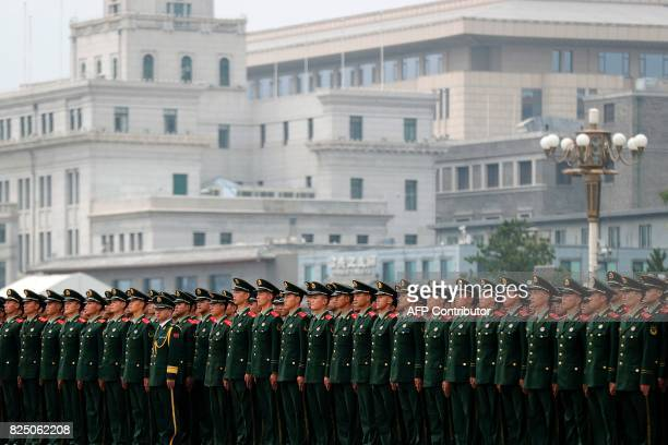 Chinese paramilitary policemen stand in formation on Tiananmen Square after attending a ceremony to commemorate the 90th anniversary of the founding...