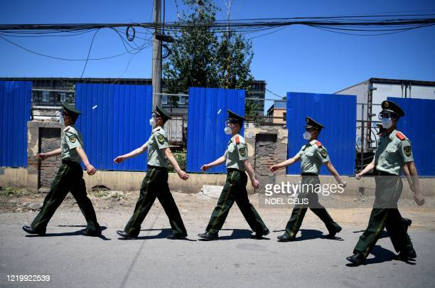 TOPSHOT Chinese paramilitary policemen wearing face masks walk past the closed Xinfadi Market in Beijing on June 14 2020 The domestic COVID19...