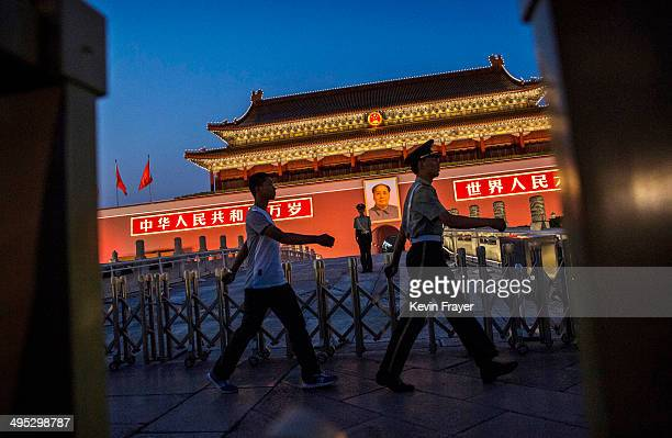 Chinese Paramilitary security force officer stands under a portrait of the late Mao Zedong as others march passed outside the Forbidden City at...