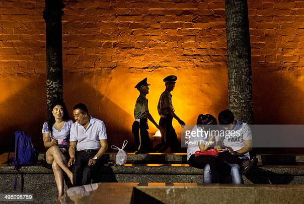 Chinese Paramilitary security force officers walk passed couples as they sit near Tiananmen Square on June 2 2014 in Beijing China Twentyfive years...