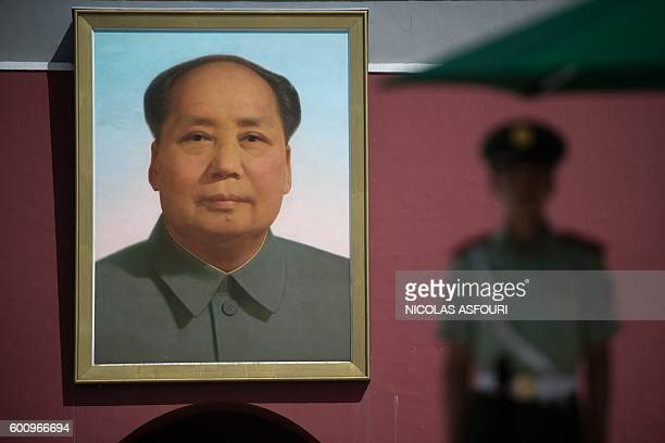 A Chinese paramilitary soldier stands guard in front of a giant portrait of Mao Zedong at the gate of the Forbidden City in Beijing on September 9...