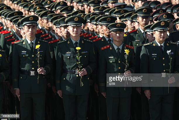 Chinese paramilitary soldiers hold flowers as they commemorate Martyrs' day in Heihe northeast China's Heilongjiang province on September 30 2015...