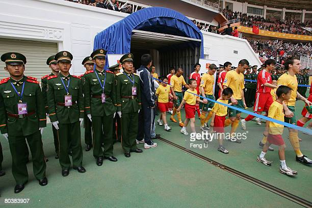 Chinese paramilitary soldiers look on as Australia and China teams enter into court during the 2010 World Cup qualifier match between Australia and...