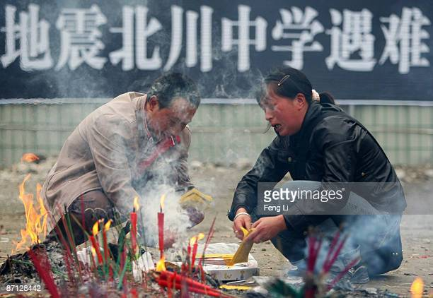 Chinese parents burn offerings to mourn their child near the ruins of the Beichuan Middle School during the one year anniversary of the Wenchuan...