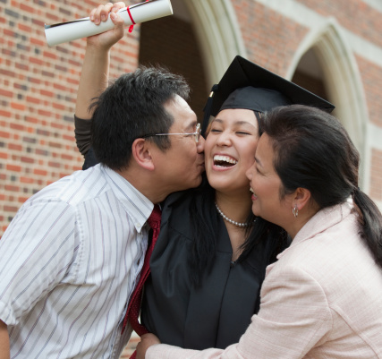 Chinese parents kissing graduate daughter - gettyimageskorea