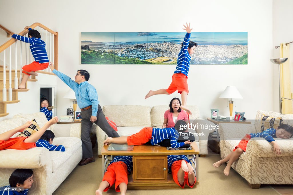 Chinese parents watching son climb all over house : Stock Photo
