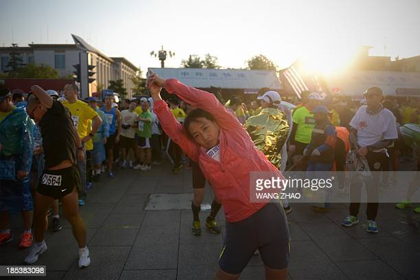 A Chinese participant prepares for the race before the start of the Beijing Marathon in the Chinese capital on October 202013 A total of 30000...