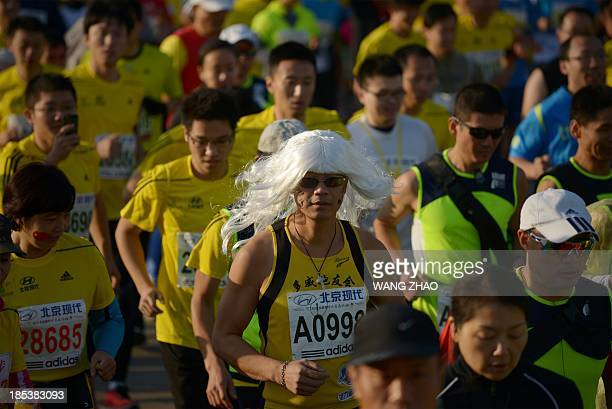 A Chinese participant wearing a wig joins the pack as they start the Beijing Marathon in the Chinese capital on October 202013 A total of 30000...