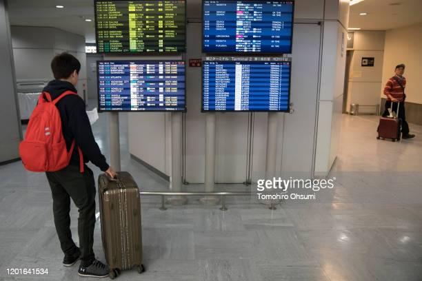 Chinese passenger looks at monitors displaying airline departure information at Narita airport on January 24, 2020 in Narita, Japan. While Japan is...