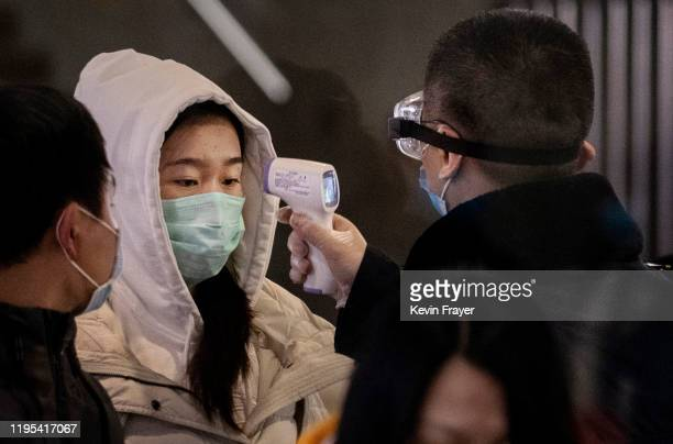 Chinese passenger that just arrived on the last bullet train from Wuhan to Beijing is checked for a fever by a health worker at a Beijing railway...