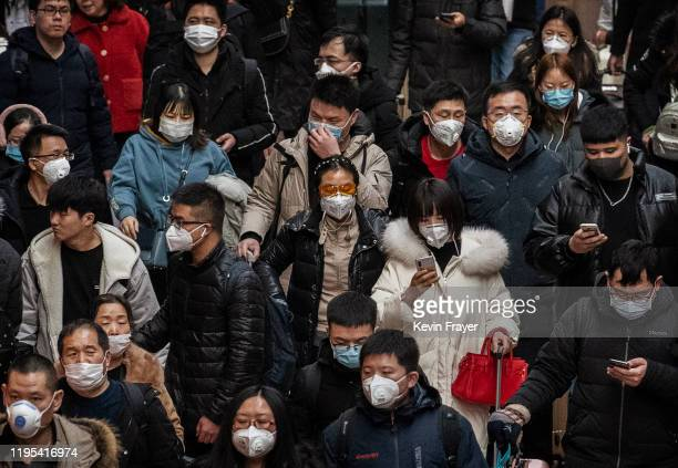 Chinese passengers almost all wearing protective masks arrive to board trains at before the annual Spring Festival at a Beijing railway station on...
