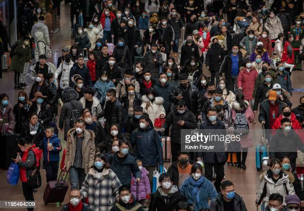 Chinese passengers most wearing masks arrive to board trains before the annual Spring Festival at a Beijing railway station on January 23 2020 in...