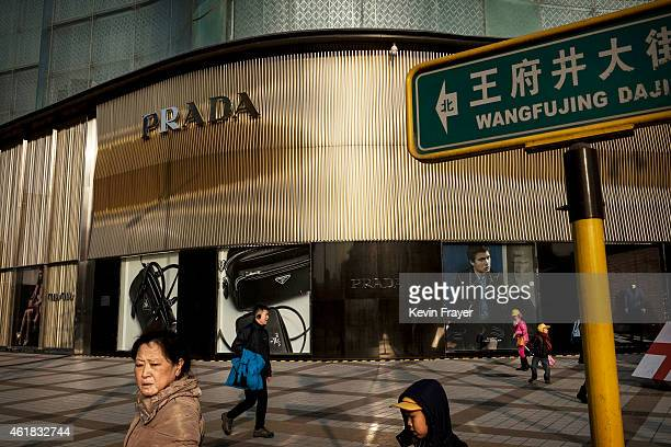 Chinese pedestrians walk passed a luxury boutique in a shopping district on January 20 2015 in central Beijing China China's economic growth slowed...