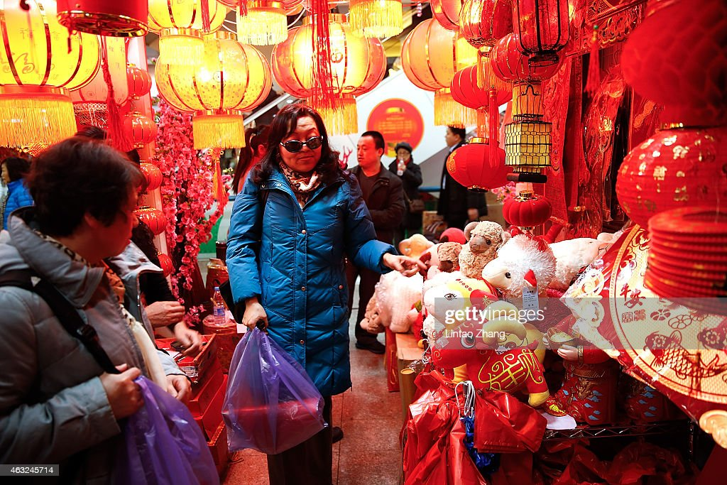 chinese people buy decorations for the upcoming chinese lunar new year of the sheep on february - Chinese Lunar New Year 2015