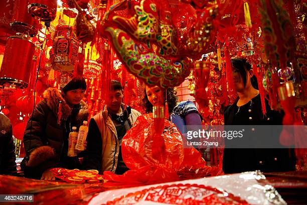Chinese people buy decorations for the upcoming Chinese Lunar New Year of the sheep on February 12 2015 in Beijing China The Chinese Lunar New Year...