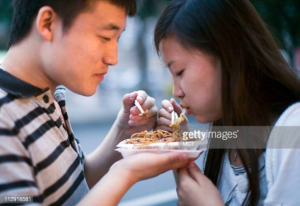 Chinese people eat dinner at Beijing's famous Donghuamen Night market where one can sample many different specialty foods found throughout China June...