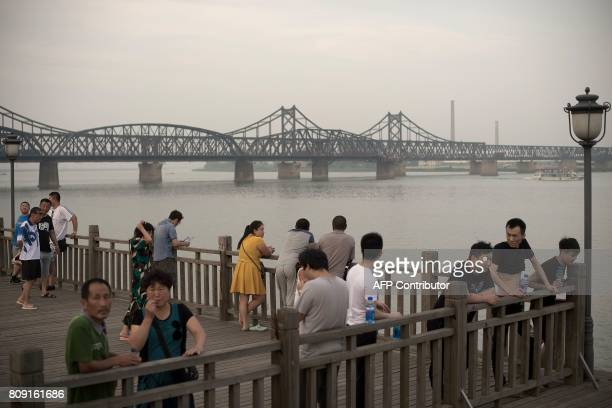Chinese people gather next to the Friendship bridge on the Yalu River connecting the North Korean town of Sinuiju and Dandong in Chinese border city...