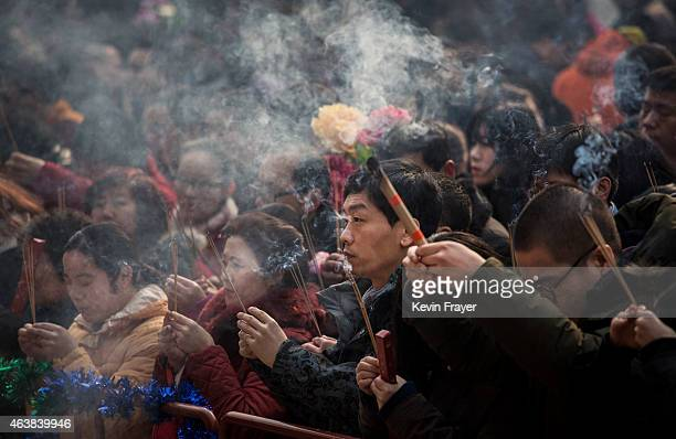 Chinese people hold incense while praying with others at the Yonghegong Lama Temple during celebrations for the Lunar New Year February 19 2015 in...