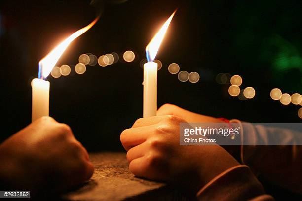 Chinese people light candles to mourn late Chinese artist Chen Yifei during a condolence ceremony on April 14 2005 at Zhouzhuang Town in Kunshan of...