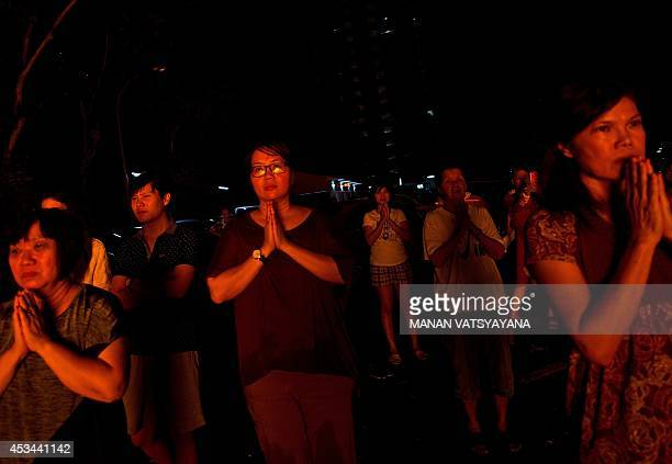Chinese people pray as they watch a statue made of paper of Chinese deity 'Da Shi Ye' or Guardian God of Ghosts burned during the Hungry Ghost...