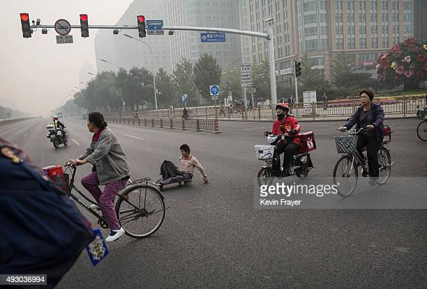 Chinese people ride across the road during a polluted morning on October 17 2015 in Beijing China As a result of industry the use of coal and...