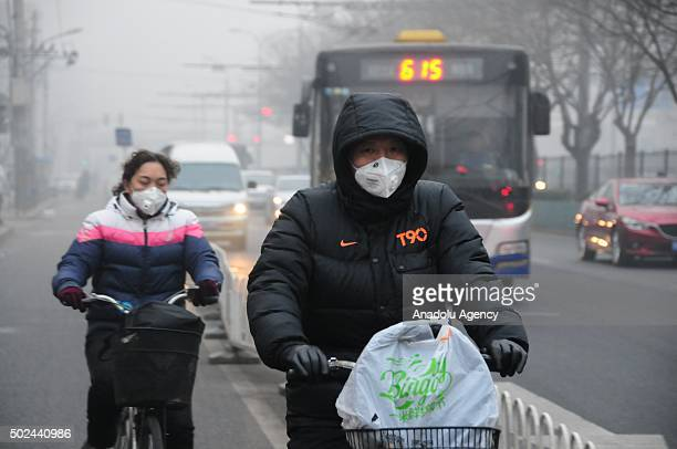 Chinese people riding bikes on a street wear masks amid heavy smog in Beijing China on December 25 2015 Hazardous smog blanketing China's northeast...