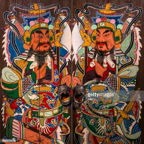 chinese people stick on spring festival couplets with carved door-gods to celebrate chinese new year - god stock pictures, royalty-free photos & images