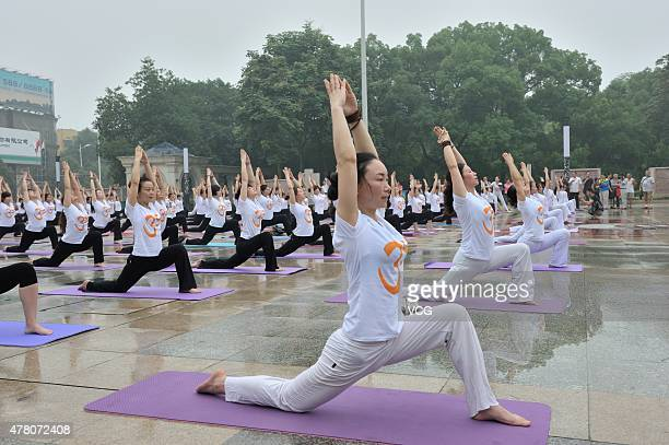 Chinese people take part in a mass yoga session to mark the first International Day of Yoga at a park on June 21 2015 in Shaoyang China