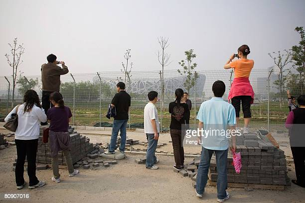 Chinese people take photos outside the National Stadium, or 'Bird's Nest', on April 29, 2008 in Beijing, China. Olympic venues 'Bird's Nest' has...