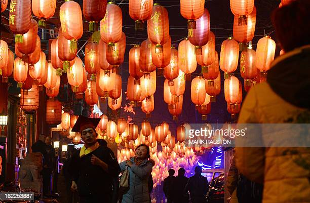 Chinese people walk beneath lanterns as the city prepares for the traditional Lantern Festival which falls on the 15th day of the Lunar New Year and...