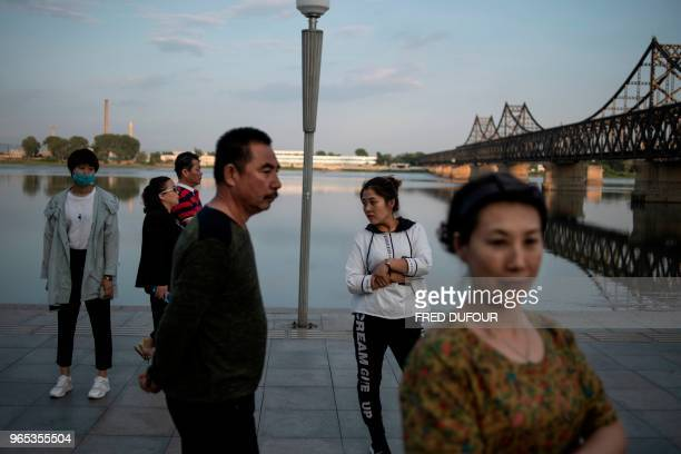 Chinese people walk on the banks of the Chinese border town of Dandong in China's northeast Liaoning province on May 30 2018 The city of Dandong...